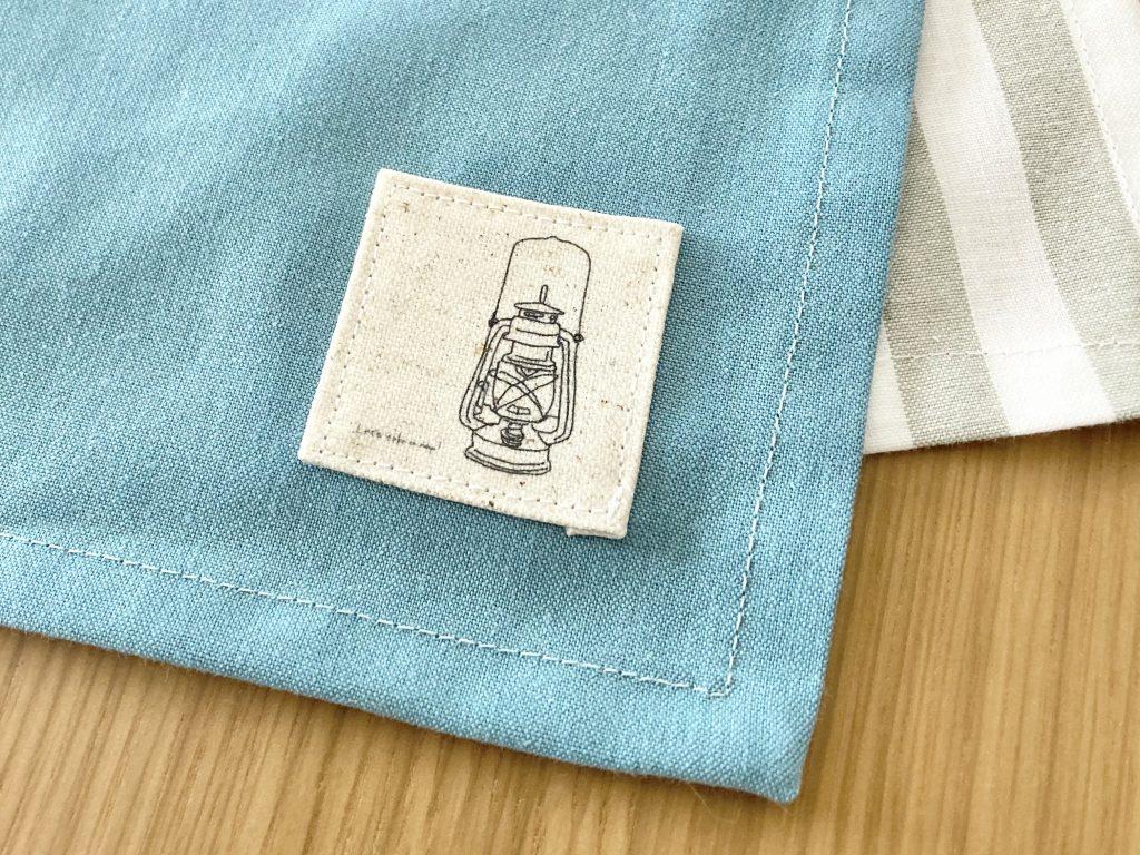 簡単!シンプルな裏地なしランチマットの作り方(額縁縫い)|タグをつける|ハンドメイド初心者のための洋裁メディア縫いナビ|丸石織物